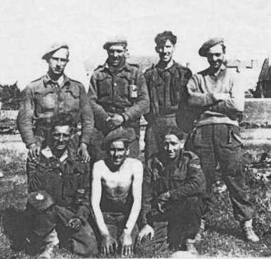 Group photograph of members of No 8 Platoon, taken on 12 September 1944 after the capture of Le Havre. Left to right: Back Row – Private Deal, Private Patrick, Private Gordon Duffin, Private Button; Front Row – Private Harris, Sergeant Sweeny, Corporal Millington. Thirty-five men of the platoon had landed on D-Day and only these seven were still on active service by 12 September. Of the seven, only two were still on active service by VE-Day.
